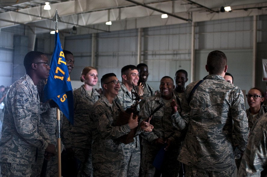 U.S. Air Force Airman of the 316th Training Squadron black rope corps celebrate after winning the drill competition in both the exhibition and regulation drill circuits in the High Bay at the Louis F. Garland Fire Academy on Goodfellow Air Force Base, Texas, June 22, 2015. The 316th TRS competed against both the 315th Training Squadrons and the 312th Training Squadrons. (U.S. Air Force photo by Senior Airman Scott Jackson)