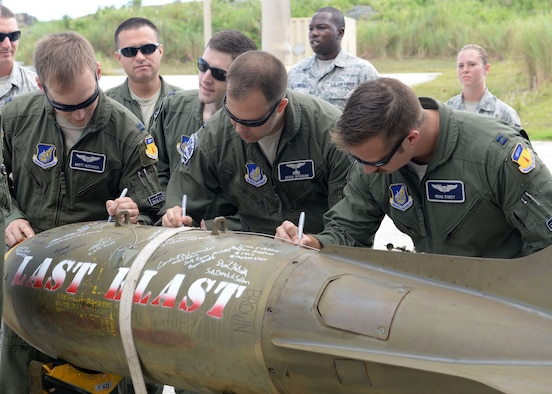 U.S. Air Force Airmen from the 20th Expeditionary Bomb Squadron sign the 'Last Blast' June 24, 2015, at Andersen Air Force Base, Guam. With the help of 36th Munitions Squadron Airmen, 20th EBS aircrew dropped the final M117 bomb in the Pacific Air Force's inventory June 26 on an uninhabited island off the coast of Guam. (U.S. Air Force photo by Airman 1st Class Joshua Smoot/Released)