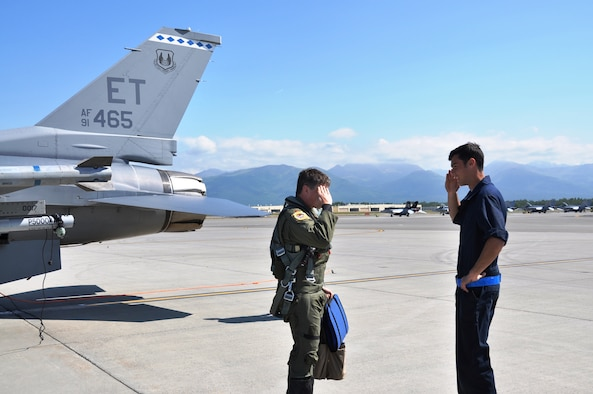 U.S. Air Force Maj Grizz Baer, 53rd Wing F-16 pilot from Wolcott, Indiana, greets Senior Airman Jeremy Fogle, 96th Aircraft Maintenance Squadron F-16 crew chief from Nazareth, Pennsylvania, prior to conducting pre-flight checks for an Exercise Northern Edge mission, June 23, 2015, Joint Base Elmendorf-Richardson, Alaska. Northern Edge is Alaska's premier joint training exercise designed to practice operations, techniques and procedures as well as enhance interoperability among the services. Thousands of service members from active duty, Reserve and National Guard units are involved. (U.S. Air Force photo by Capt. Tania Bryan/Released)