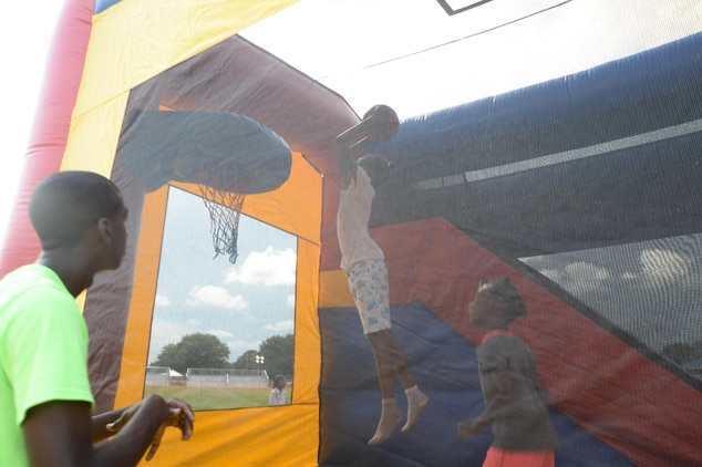 A child leaps high in the air to dunk a basketball during the Independence Day celebration, June 26, held at Marine Corps Logistics Base Albany.