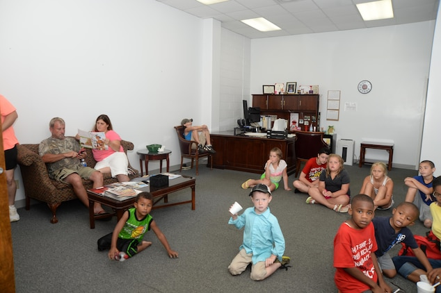 Several children and adults take refuge in Building 3500 office space June 26 after base officials temporarily suspend the Independence Day celebration due to lightning.