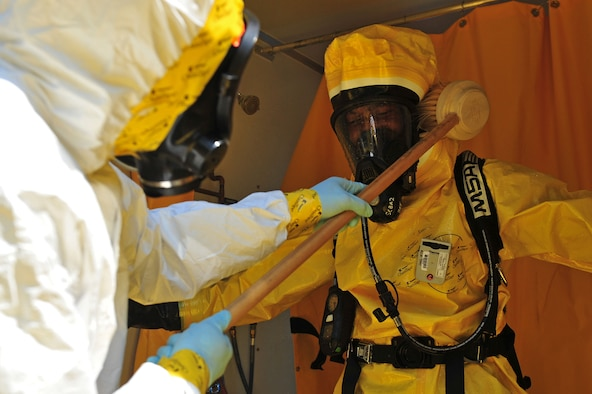 Senior Airman Oshane Wint, left, 4th Aerospace Medicine Squadron bioenvironmental engineer, decontaminates Maj. Michael Smith, 4th AMDS bioenvironmental engineering flight commander, during an integrated base emergency response capabilities training exercise, June 25, 2015, at Seymour Johnson Air Force Base, North Carolina. Individuals undergo decontamination upon return from a hazardous environment to prevent further spread of contamination. (U.S. Air Force photo/Senior Airman John Nieves Camacho)
