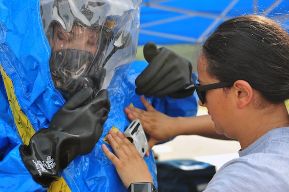 Senior Airman Andrea Spanjer, right, 4th Aerospace Medicine Squadron bioenvironmental engineer, attaches an electronic personal dosimeter to Airman 1st Class Amanda Vazquez-Lloret, 4th AMDS bioenvironmental engineer, during an integrated base emergency response capabilities training exercise, June 24, 2015, at Seymour Johnson Air Force Base, North Carolina. An EPD monitors exposure to radiation levels in real time and emits an audible and visual alarm when radiation presence is high. (U.S. Air Force photo/Senior Airman John Nieves Camacho)