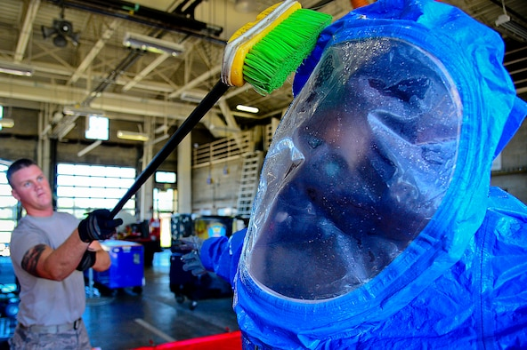 """A 6th Civil Engineering Squadron fire fighter scrubs an Airmen in a Level A hazardous material suit during a joint responder training at MacDill Air Force Base, Fla., June 24, 2015. The HAZMAT decontamination line ensures that all personnel leaving the hazardous material """"hot zone"""" are properly cleaned of any and all contaminants. (U.S. Air Force photo by Senior Airman Ned T. Johnston/Released)"""