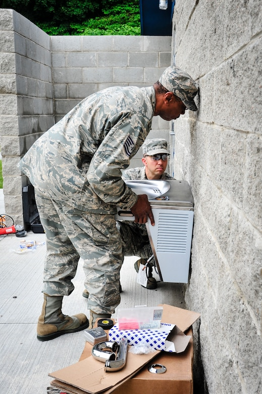 113th Civil Engineer Squadron Water and Fuel System Maintenance specialists Tech. Sgt. Rodney Allen and Staff Sgt. Michael Kammerer install a new water fountain while deployed to the U.S. Coast Guard Academy for a deployment for training.  (U.S. Air National Guard photo by Chief Master Sgt. Andrew Baker)