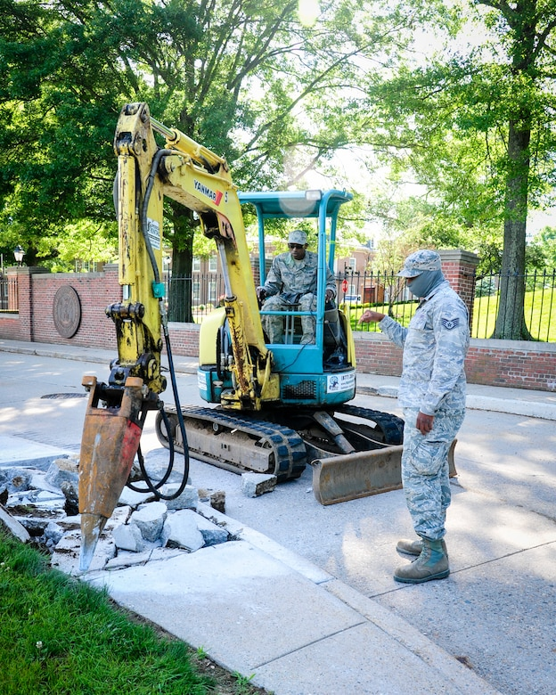 113th Civil Engineer Squadron Heavy Equipment Operators Staff Sgt. Keenan Willis and Airman 1st Class Timothy Blake replace an old section of sidewalk during a deployment for training to the U.S Coast Guard Academy.  (U.S. Air National Guard photo by Chief Master Sgt. Andrew Baker)