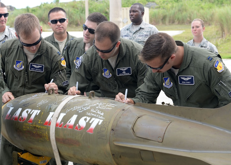 Airmen from the 20th Expeditionary Bomb Squadron sign the 'Last Blast' June 24, 2015, at Andersen Air Force Base, Guam. With the help of 36th Munitions Squadron Airmen, 20th EBS aircrew dropped the final M117 bomb in the Pacific Air Force's inventory June 26 on an uninhabited island off the coast of Guam. (U.S. Air Force photo by Airman 1st Class Joshua Smoot/Released)