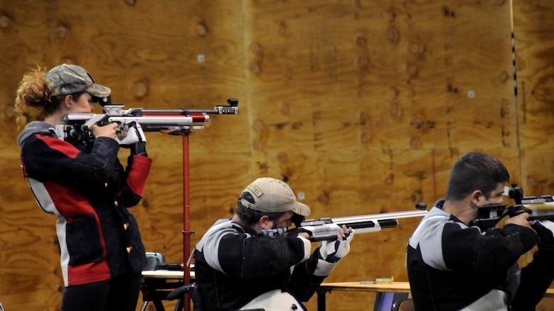 Medically retired Marine Sgt. Janae Piper, Air Force Staff Sgt. Seth Pena and Air Force Master Sgt. Daniel Waugh get ready to compete in the air rifle competition at the 2015 DoD Warrior Games at Marine Corps Base Quantico, Virginia, June 26, 2015. Piper earned the gold medal, Waugh earned the silver medal and Pena earned the bronze medal for the event.