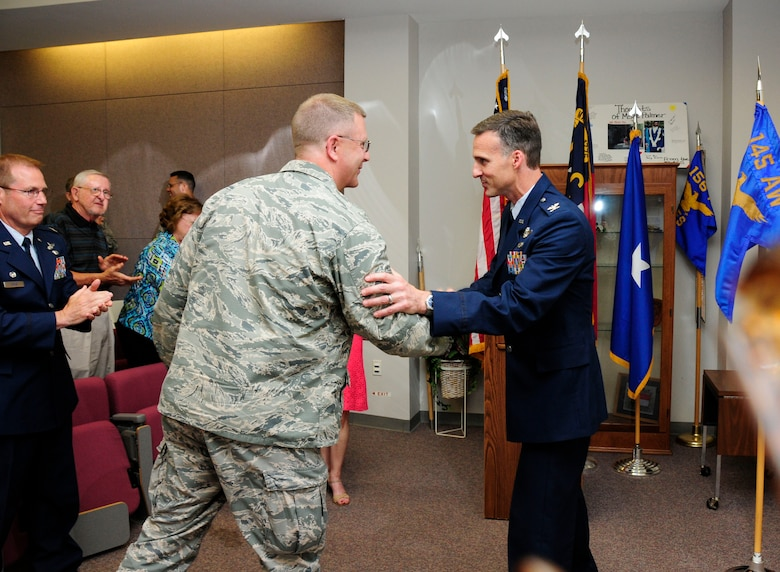 After assuming command of the 145th Operations Group, U.S. Air Force Col. Joseph H. Stepp IV is congratulated by Brig. Gen. Roger E. Williams, Jr., Assistant Adjutant General – Air, during a change of command ceremony held at the North Carolina Air National Guard Base, Charlotte Douglas International Airport; June 6, 2015. (U.S. Air National Guard photo by Master Sgt. Patricia F. Moran, 145th Public Affairs/Released)