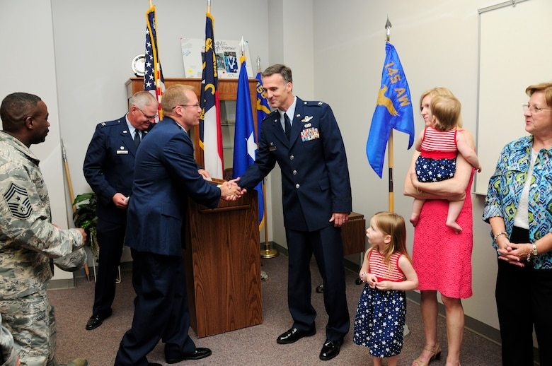 U.S. Air Force Col. Charles D. Davis III congratulates Col. Joseph H. Stepp IV, commander, 145th Operations Group, after Stepp's promotion ceremony held at the North Carolina Air National Guard Base, Charlotte Douglas International Airport; June 6, 2015. (U.S. Air National Guard photo by Master Sgt. Patricia F. Moran, 145th Public Affairs/Released)