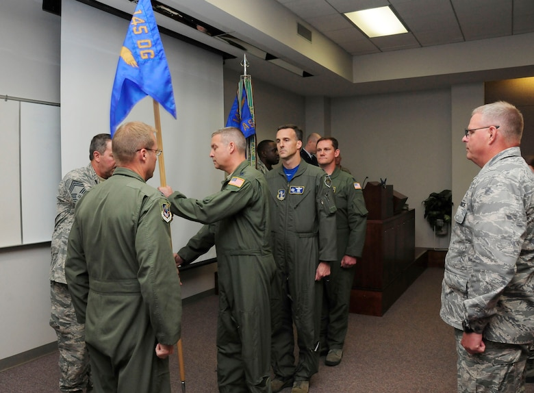 U.S. Air Force Lt. Col. Bradley E. Holbrooks, passes guidon to Chief Master Sgt. Andrew Huneycutt, 145th Airlift Wing, loadmaster supervisor, after assuming command of the 145th Operations Support Squadron during a change of command ceremony held at the North Carolina Air National Guard base, Charlotte Douglas International Airport, June 6, 2015. (U.S. Air National Guard photo by Master Sgt. Patricia F. Moran, 145th Public Affairs/Released