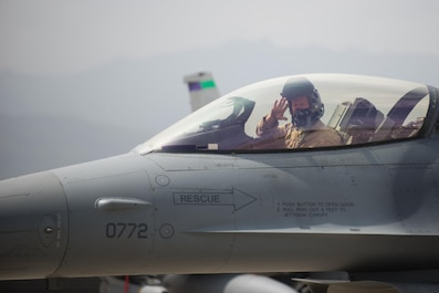 U.S. Air Force Brig. Gen. Mark D. Kelly, 455th Air Expeditionary Wing commander, waves while taxing in an F-16 Fighting Falcon aircraft during his final flight as the 455th AEW Commander at Bagram Airfield, Afghanistan, June 28, 2015 The final flight is an aviation tradition in which aircrew members, upon completion of their last flight with the wing are met and hosed down with water. (U.S. Air Force photo by Tech. Sgt. Joseph Swafford/Released)