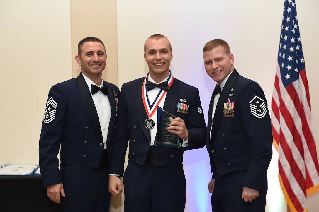 Chief Master Sgt. Brian Kruzelnick, 460th Space Wing command chief, and Master Sgt. Christopher Smith,460th Space Communications Squadron first sergeant, congratulate Senior Airman Mitchell Ciccarelli, Air Reserve Personnel Center casualty services technician, during the Buckley Airman Leadership School Class 15-E graduation June 25, 2015, at the Leadership Development Center on Buckley Air Force Base, Colo. This graduation represents an important part of the enlisted force professional military education, teaching valuable skills required for supervisors. (U.S. Air Force photo by Airman 1st Class Samantha Meadors)
