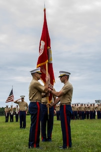 Major Andrew Gourgoumis, outgoing commanding officer of Recruiting Station Portsmouth, New Hampshire, hands the Marine Corps colors to Maj. Stephen Boada during the change of command ceremony, June 26. Boada is coming from his position as inspector-instructor of Battery P., 5th Battalion, 14th Marines in Spokane, Washington, and Gourgoumis is heading to the Command and Staff College aboard Marine Corps Base Quantico, Virginia.