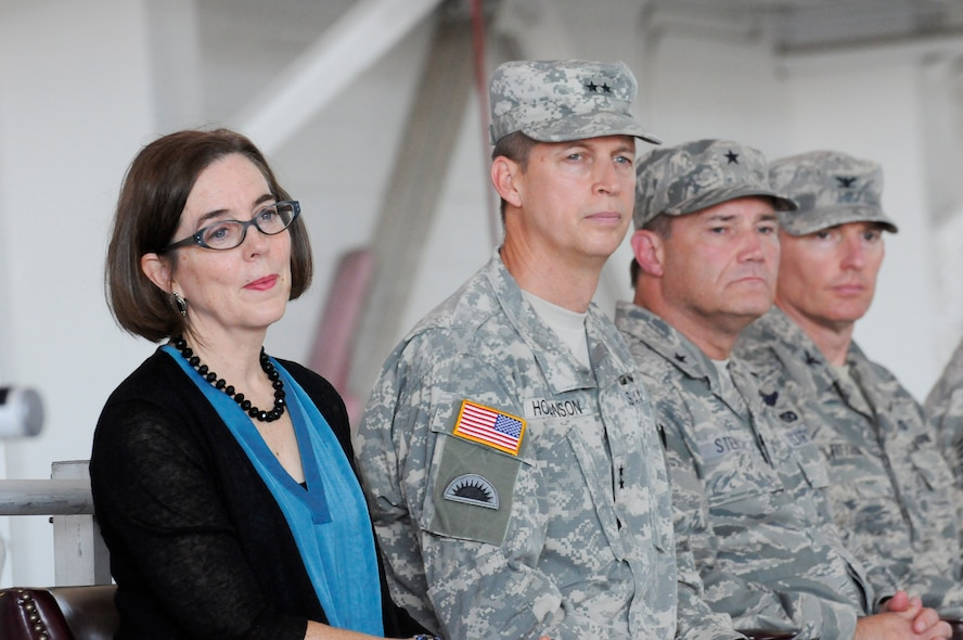 Members of the official party, left to right, Oregon Governor Kate Brown, Oregon Adjutant General Daniel Hokanson, Oregon Air National Guard Commander Michael Stencel and 142nd Fighter Wing Commander Col. Paul Fitzgerald listen to music performed by the 234th Army National Guard Band during the 142nd Fighter Wing mobilization ceremony, June 26, 2015, Portland Air National Guard Base, Ore. (U.S. Air National Guard photo by Tech. Sgt. John Hughel, 142nd Fighter Wing Public Affairs/Released)