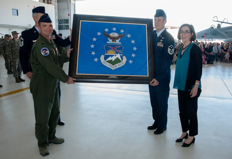 Oregon Air National Guard Lt. Col. Sean Sullivan, 123rd Fighter Squadron commander, 142nd Fighter Wing, left, presents the unit flag of the 142nd Fighter Wing to Oregon Governor Kate Brown during the unit's mobilization ceremony, June 26, 2015, Portland Air National Guard Base, Ore. (U.S. Air National Guard photo by Tech. Sgt. John Hughel, 142nd Fighter Wing Public Affairs/Released)