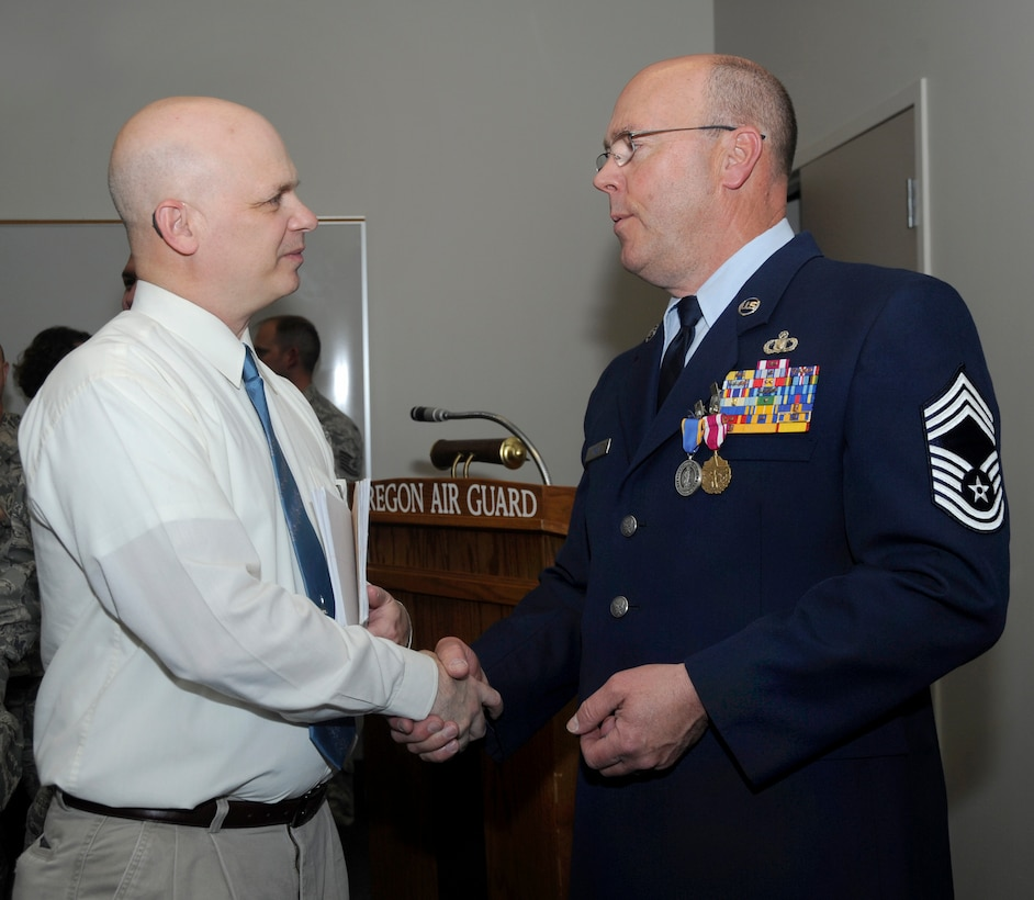 Retired Air Force Lt. Col. Terry Popravak, 142nd Fighter Wing volunteer base historian, left, congratulates retired Chief Master Sgt. Patrick Tracy, right, at the conclusion of his formal retirement ceremony, May 2, 2015, Portland Air National Guard Base, Ore. Tracy was assigned to the 142nd Fighter Wing Operations Group, serving as the senior enlisted leader and also was the Team Chief for the Air National Guard's F-15 Eagle Weapons System Council, Aircrew Flight Equipment. (U.S. Air National Guard by Tech. Sgt. John Hughel, 142nd Fighter Wing Public Affairs Department)