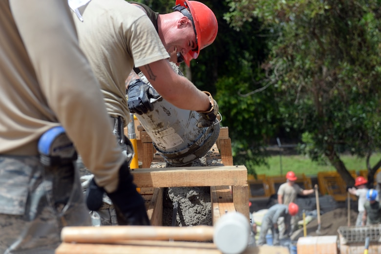 U.S. Marine Staff Sgt. Andrew Smith, a combat engineer with a 271st Marine Wing Support Squadron, 2nd Marine Air Wing, pours cement into a wood frame to create a bond beam for the new two-room schoolhouse at the Gabriela Mistral school construction site in Ocotes Alto, Honduras, June 22, 2015. The school project is one part of the NEW HORIZONS Honduras 2015, an annual humanitarian and training exercise put on by U.S. Southern Command. NEW HORIZONS was launched in the 1980s and is an annual joint humanitarian assistance exercise that U.S. Southern Command conducts with a partner nation in Central America, South America or the Caribbean. The exercise improves joint training readiness of U.S. and partner nation civil engineers, medical professionals and support personnel through humanitarian assistance activities. (U.S. Air Force photo by Capt. David J. Murphy/Released)