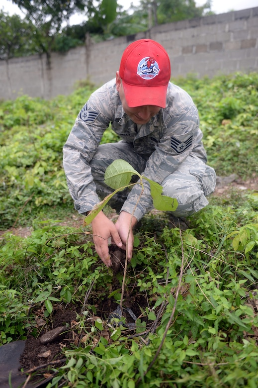 U.S. Staff Sgt. David Mosley, 823rd Expeditionary RED HORSE Squadron vehicle maintenance journeyman, out of Hurlburt Field, Fla., helps put dirt at the base of a newly planted tree during the National Tree Day celebration at Rafeal Peneda Ponce School in Trujillo, Honduras, June 19, 2015. Mosley is a member of the NEW HORIZONS Honduras 2015 training exercise which is providing support throughout the Trujillo and Tocoa regions of Honduras by building a new two-classroom schoolhouse in Ocotes Alto, drilling a well in Honduras Aguan, and proving general medical support. NEW HORIZONS was launched in the 1980s and is an annual joint humanitarian assistance exercise that U.S. Southern Command conducts with a partner nation in Central America, South America or the Caribbean. The exercise improves joint training readiness of U.S. and partner nation civil engineers, medical professionals and support personnel through humanitarian assistance activities. (U.S. Air Force photo by Capt. David J. Murphy/Released)