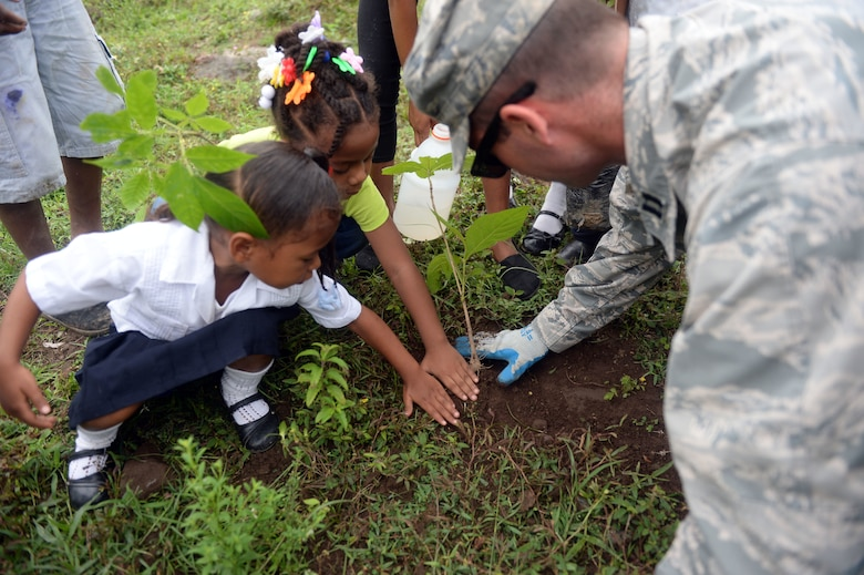 U.S. Air Force Capt. Austin McKinney, 12th Air Force assessments officer in charge, helps students plant trees during the National Tree Day celebration at Rafeal Peneda Ponce School in Trujillo, Honduras, June 19, 2015. McKinney is a member of the NEW HORIZONS Honduras 2015 training exercise which is providing support throughout the Trujillo and Tocoa regions of Honduras by building a new two-classroom schoolhouse in Ocotes Alto, drilling a well in Honduras Aguan, and proving general medical support. NEW HORIZONS was launched in the 1980s and is an annual joint humanitarian assistance exercise that U.S. Southern Command conducts with a partner nation in Central America, South America or the Caribbean. The exercise improves joint training readiness of U.S. and partner nation civil engineers, medical professionals and support personnel through humanitarian assistance activities. (U.S. Air Force photo by Capt. David J. Murphy/Released)