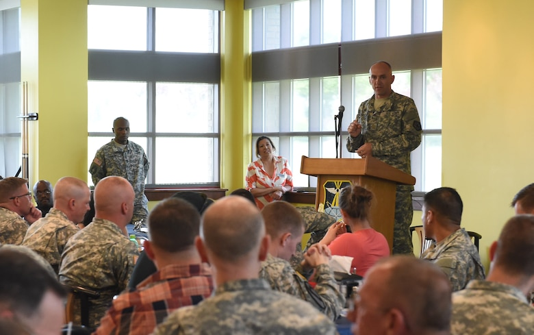 Maj. Jeremy McHugh, 743rd Military Intelligence Battalion member, speaks with U.S. Army members during the Team Buckley Military Heritage Series: Army Salute celebration June 26, 2015, at Panther Den on Buckley Air Force Base, Colo. The Army Salute, which included displays, brief presentations and free food, was held to celebrate the Army's 240th birthday and its history on Buckley AFB. (U.S. Air Force photo by Airman 1st Class Samantha Meadors/Released)