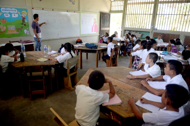 Cristian Suazo teaches Gabriela Mistral third graders math at the Gabriela Mistral School in Ocotes Alto, Honduras, June 16, 2015. Gabriela Mistral is the site of a new two-room classroom being built by U.S. Air Force Airmen from the 823rd Expeditionary RED HORSE Squadron, and U.S. Marines from the 271st Marine Wing Support Squadron, 2nd Marine Air Wing, as part of the NEW HORIZONS Honduras 2015 training exercise going on throughout the Trujillo and Tocoa, Honduras regions. NEW HORIZONS was launched in the 1980s and is an annual joint humanitarian assistance exercise conducted by U.S. Southern Command with a partner nation in Central America, South America or the Caribbean. The exercise improves joint training readiness of U.S. and partner nation civil engineers, medical professionals and support personnel through humanitarian assistance activities. (U.S. Air Force photo by Capt. David J. Murphy/Released)