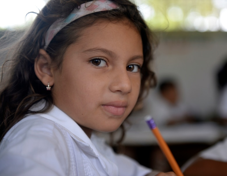 A Gabriela Mistral third grader poses for a photo at the Gabriela Mistral School in Ocotes Alto, Honduras, June 16, 2015. Gabriela Mistral is the site of a new two-room classroom being built by U.S. Air Force Airmen from the 823rd Expeditionary RED HORSE Squadron, and U.S. Marines from the 271st Marine Wing Support Squadron, 2nd Marine Air Wing, as part of the NEW HORIZONS Honduras 2015 training exercise going on throughout the Trujillo and Tocoa, Honduras regions. NEW HORIZONS was launched in the 1980s and is an annual joint humanitarian assistance exercise conducted by U.S. Southern Command with a partner nation in Central America, South America or the Caribbean. The exercise improves joint training readiness of U.S. and partner nation civil engineers, medical professionals and support personnel through humanitarian assistance activities. (U.S. Air Force photo by Capt. David J. Murphy/Released)