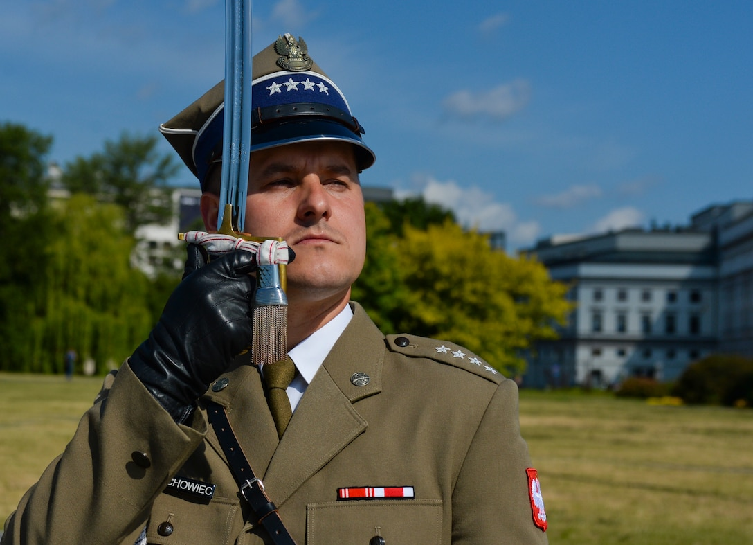 A Polish air force ceremonial guardsman salutes with a saber as Deborah Lee James, Secretary of the U.S. Air Force, participates in a wreath-laying ceremony at the Tomb of the Unknown Soldier in Warsaw, Poland, June 22, 2015. The Secretary completed a visit of installations through Europe June 24, 2015, to meet Airmen, community leaders and allied and partner nation defense chiefs. (U.S. Air Force photo by Staff Sgt. Joe W. McFadden/Released)