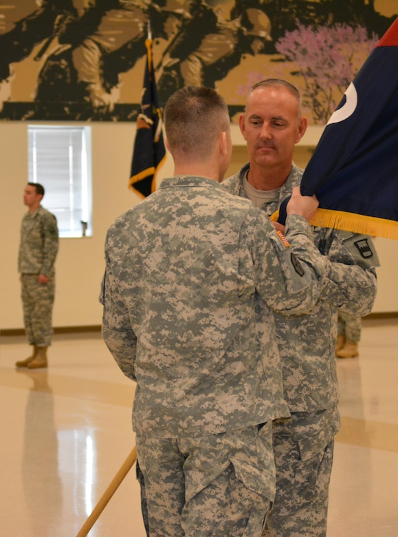 Command Sgt. Maj. Jeffry Darlington, acting senior noncommissioned officer 800th Logistics Support Brigade, (facing camera) passes the brigade colors to Col. Howard C. W. Geck, the outgoing commander during a change of command ceremony Mustang, Okla., June 28, 2015. Col. Bradly M. Boganowski replaced Geck as commander.