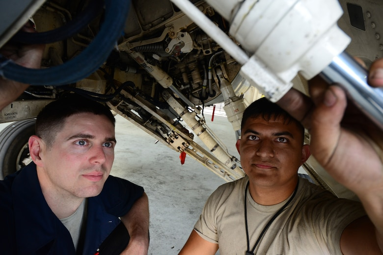 Staff Sgt Dennis Lamm, 8th. Maintenance Squadron inspection section floor chief, and Airman 1st Class Emiliano Silva, 8th MXS inspection section team member, inspect the landing gear of an F-16 Fighting Falcon at Kunsan Air Base, Republic of Korea June 9, 2015. Airmen from the 8th MXS inspection section perform phase inspections to take an in-depth look at aircraft before and after flight. Phase inspections are performed on aircraft every 400 flight hours and involve procedural maintenance actions that require robust attention to detail. (U.S. Air Force photo by Staff Sgt. Nick Wilson/Released)