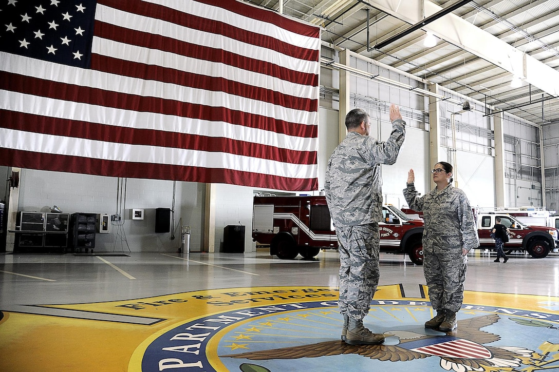 U.S. Air Force Lt. Col. Derek Ferland, 312th Training Squadron Commander, reenlists Staff Sgt. Laura R. McFarlane, 17th Training Wing Public Affairs photojournalist craftsman, at the Louis F. Garland Department of Defense Fire Academy on Goodfellow Air Force Base, Texas, June 24, 2105. This was McFarlane's third reenlistment. (U.S. Air Force photo by Tech. Sgt. Austin Knox/Released)
