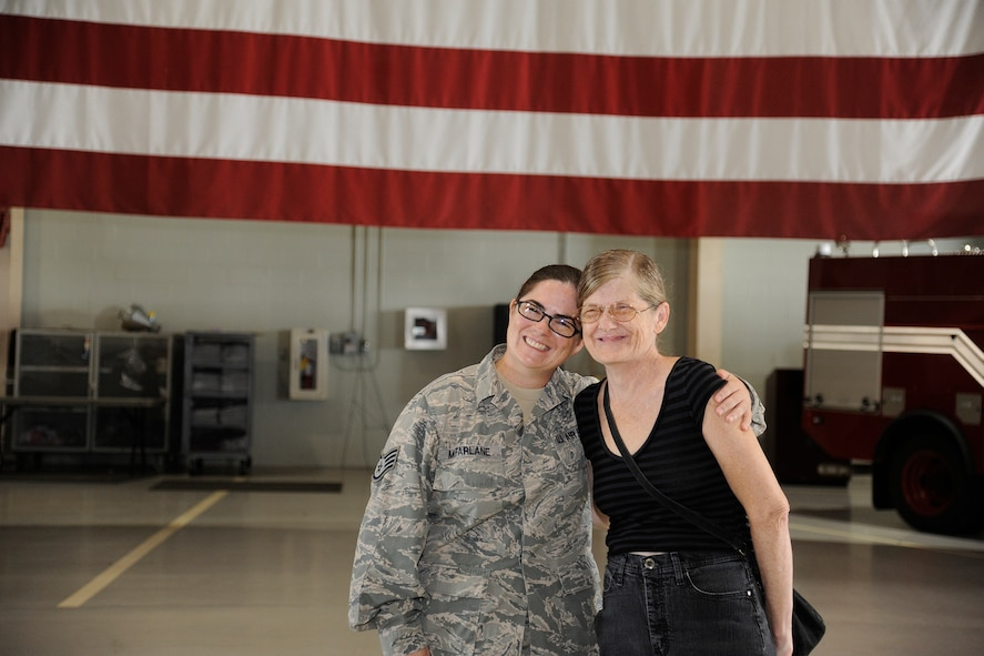 U.S. Air Force Staff Sgt. Laura R. McFarlane, 17th Training Wing Public Affairs photojournalist craftsman, poses with Susan G. McFarlane, at the Louis F. Garland Department of Defense Fire Academy on Goodfellow Air Force Base, Texas, June 24, 2105. Staff Sgt. McFarlane reenlisted after serving 13 years. (U.S. Air Force photo by Tech. Sgt. Austin Knox/Released)