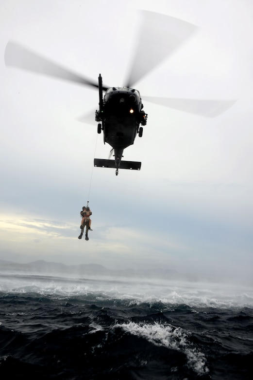 A 320th Special Tactics Squadron pararescueman hoists a Gold Team member out of the water into a Kadena-based HH-60 from the 33rd Rescue Squadron during Gold Thunder 2.0 held at Camp Hansen July 24, 2015.  The exercise scenario ended with a sanitation and evacuation of the forward operating location by water via rotary wing aircraft.  Gold Thunder 2.0 is a humanitarian assistance/disaster relief scenario exercise put together to train the combat mission support personnel in land and water navigation, establishing a special tactics operations center and a forward operating logistics hub along with other skills such as all-terrain vehicle qualification training, Krav Maga training and exfiltration capabilities with rotary wing aircraft. (U.S. Air Force photo by Tech. Sgt. Kristine Dreyer)