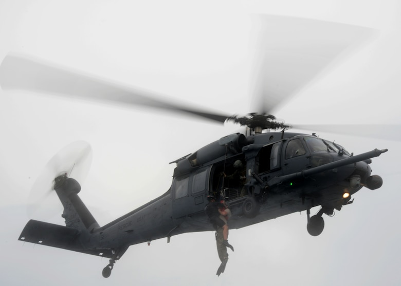 A 320th Special Tactics Squadron pararescueman hoists a Gold Team member out of the water into a Kadena-based HH-60 from the 33rd Rescue Squadron during Gold Thunder 2.0 held at Camp Hansen July 24, 2015.  The exercise scenario ended with a sanitation and evacuation of the forward operating location by water via rotary wing aircraft.  Gold Thunder 2.0 is a humanitarian assistance disaster/relief scenario exercise put together to train the combat mission support personnel in land and water navigation, establishing a special tactics operations center and a forward operating logistics hub along with other skills such as all-terrain vehicle qualification training, Krav Maga training and exfiltration capabilities with rotary wing aircraft. (U.S. Air Force photo by Tech. Sgt. Kristine Dreyer)