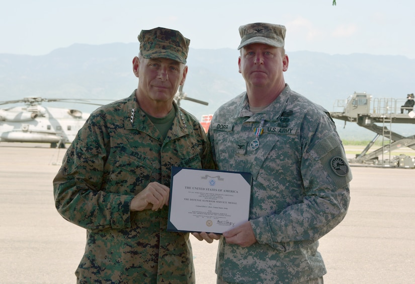 Gen. John Kelly, U.S. Southern Command commander, and Col. Kirk Dorr, Joint Task Force – Bravo outgoing commander, pose for a photo following an award presentation for Dorr June 30, 2015, at Soto Cano Air Base, Honduras. Dorr received the Defense Superior Service Medal for his year in command, prior to the JTF – Bravo change of command ceremony. (U.S. Air Force photo by Martin Chahin)