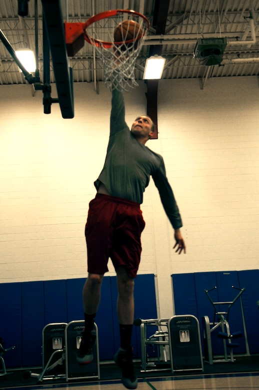 Senior Airman Tyler Cerney, 544th Intelligence, Surveillance and Reconnaissance Group, detachment 1, intelligence analyst, dunks a basketball, June 29, 2015, Vandenberg Air Force Base, Calif. Although being a Unit Fitness Program Monitor, and trained Physical Training Leader, can be demanding, Cerney not only accepts the responsibility – he relishes it. (U.S. Air Force photo by Senior Airman Shane Phipps/Released)