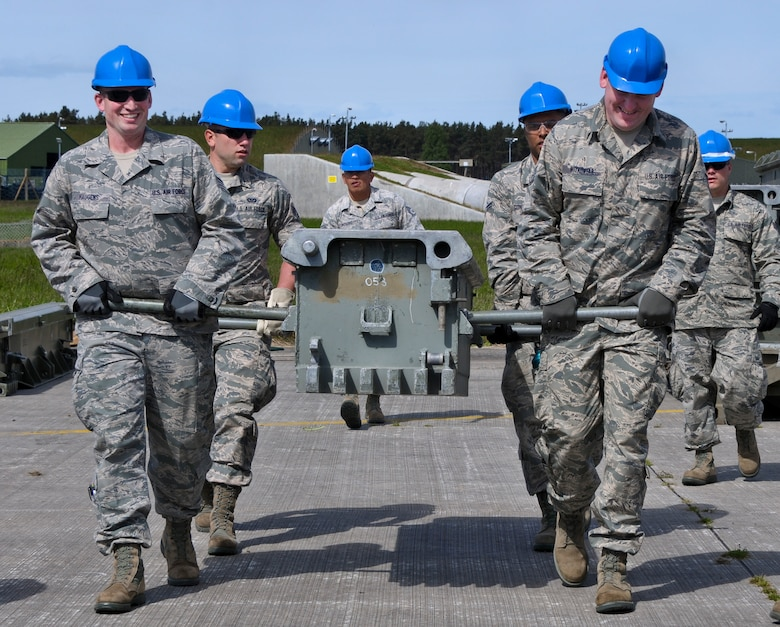 U.S. Air Force Airmen with the Civil Engineering Squadron of the 128th Air Refueling Wing, Wisconsin Air National Guard, work together to move training equipment June 9, 2015, at Kinloss Barracks in Morayshire, Scotland, United Kingdom, in support of Exercise Flying Rose. Exercise Flying Rose is an exchange exercise between the U.S. Air National Guard and British Army, where forces deploy to one another's countries and work to complete construction-related tasks. (U.S. Air National Guard photo by Airman 1st Class Morgan R. Lipinski/Released)