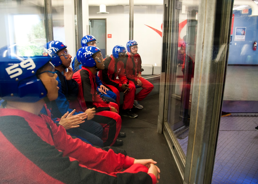 DENVER, Colo. – Members of Peterson Air Force Base wait for their turn to fly in the wind tunnel at IFly Indoor Skydiving for a Peterson Chapel retreat, June 19, 2015. Members of Peterson Air Force Base watch as one of the IFly World instructors fly around in the wind tunnel during a Peterson Chapel event, June 19, 2015. Peterson leadership picked their top performers to participate in a day retreat to indoor skydive, eat lunch and discuss the stress of military life and resources available. (U.S. Air Force photo by Senior Airman Tiffany DeNault)