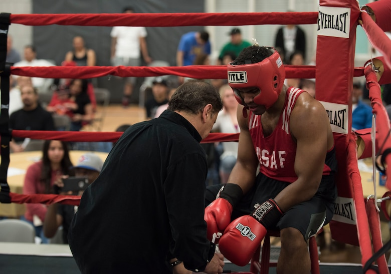 Senior Airman Martin E. Bills III, right, 366th Security Forces Squadron response force leader, listens to his coach's advice after a difficult second round during his fight at the Sorenson Center in Salt Lake City, March 28, 2015. Bills explained he exhausted himself in the first round of the fight and ran out of energy by the third round. He didn't let himself give up though; he expressed his family drives him to push forward despite the opposition. (U.S. Air Force photo by Airman 1st Class Jeremy L. Mosier/Released)