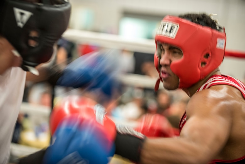 Senior Airman Martin E. Bills III, 366th Security Forces Squadron response force leader, trades punches with his opponent during the fight at the Sorenson Center in Salt Lake City, March 28, 2015. This was the first fight Bills has competed in since making the All Air Force Boxing Team. (U.S. Air Force photo by Airman 1st Class Jeremy L. Mosier/Released)