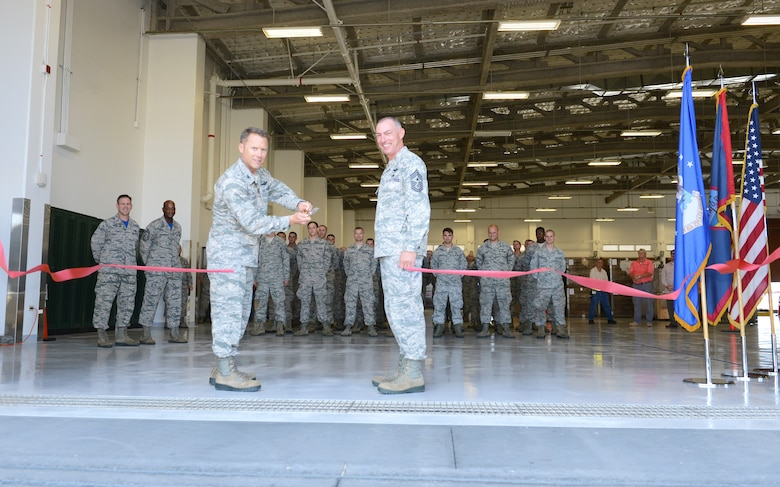 Col. Casey Eaton, 515th Air Mobility Operations commander, cuts the ribbon during the opening of the new air freight terminal June 26, 2015, at Andersen Air Force Base, Guam.  The new facility offers more working and storage space to enhance capabilities for the Pacific theater. (U.S. Air Force photo by Airman 1st Class Arielle Vasquez/Released)