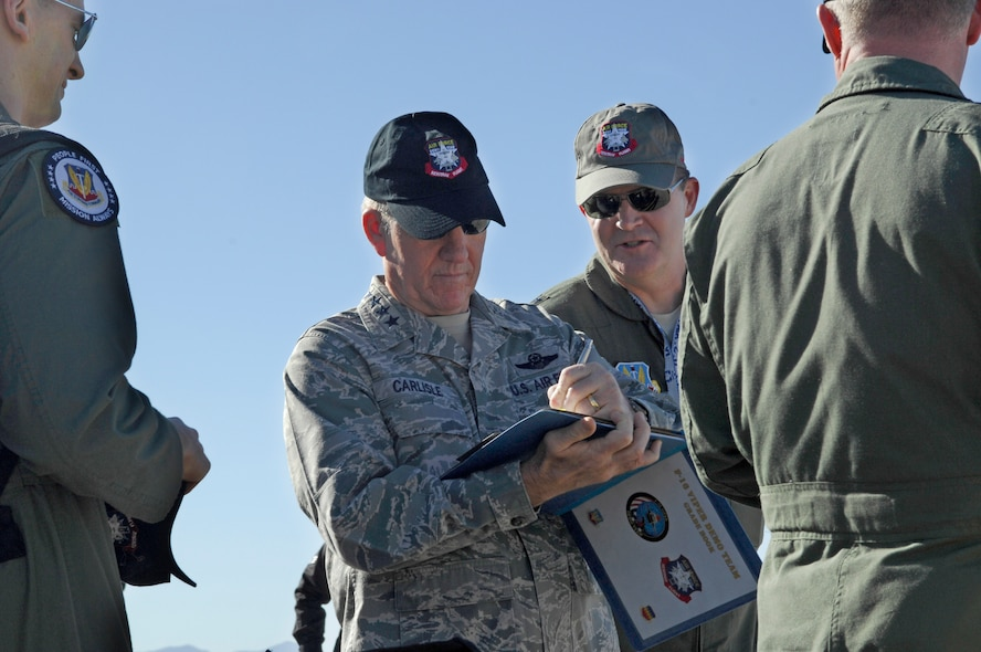 U.S. Air Force General Hawk Carlisle, Commander of Air Combat Command, signs the gradebook on the flight line during the Heritage Flight Training Conference at Davis-Monthan Air Force Base, Ariz., Feb, 27, 2015. The paperwork certifies the F-16 pilot as the Viper Demonstration Team pilot. (U.S. Air Force photo by Airmen 1st Class Cheyenne Morigeau/Released)