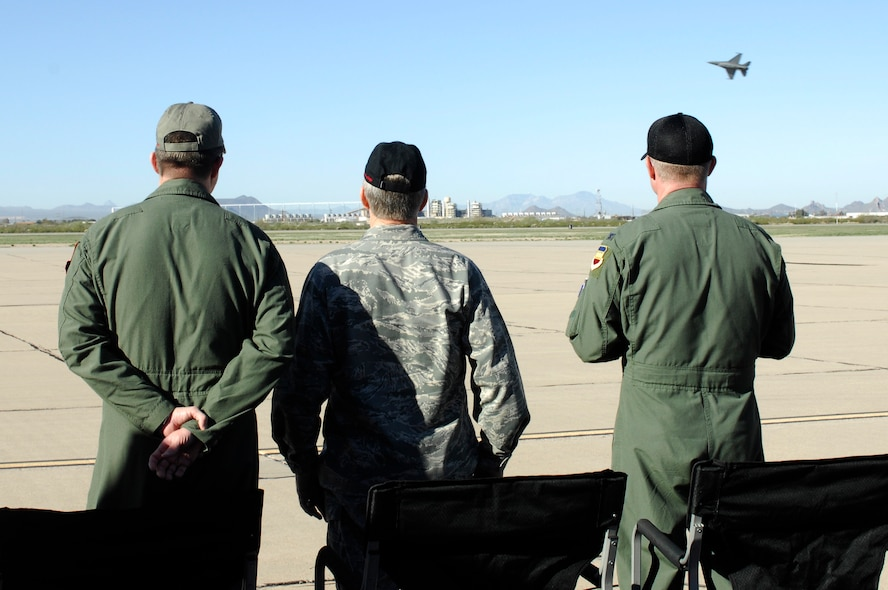U.S. Air Force General Hawk Carlisle (center), Commander of Air Combat Command, observers an F-16 Fighting Falcon fly over during the Heritage Flight Training Conference at Davis-Monthan Air Force Base, Ariz., Feb, 27, 2015. Carlisle certified a Viper Demonstration Team pilot, allowing him to fly in future airshows.  (U.S. Air Force photo by Airmen 1st Class Cheyenne Morigeau/Released)