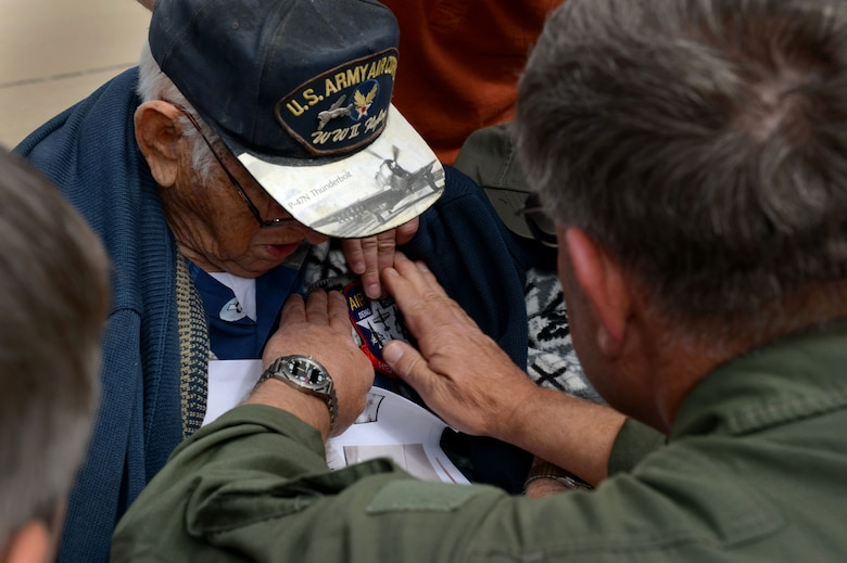 Retired Air National Guard Chief Warrant Officer 2 Robert Hertel, receives a Heritage Flight patch from Tom Gregory, P-47 Thunderbolt HF pilot during the Heritage Flight Training and Certification Course Feb. 28, 2015, at Davis-Monthan Air Force Base, Ariz. Hertel, a 92-year-old veteran, flew the Thunderbolt during World War II and had not seen one since his retirement in the 1960's. (U.S. Air Force photo/Senior Airman Jensen Stidham)