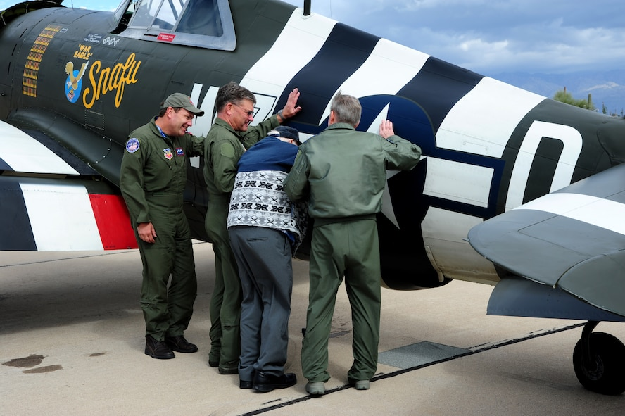 (Center) Retired Chief Warrant Officer 2 Robert Hertel, 92-year-old World War II veteran, places his hand on the side of a P-47 Thunderbolt for the first time in years with the assistance of Charles Hainline, Tom Gregory, both P-47 Thunderbolt Heritage Flight pilots, and U.S. Air Force General Hawk Carlisle, Commander of Air Combat Command, at Davis-Monthan Air Force Base, Ariz., Feb. 28, 2015. Hertel was given the opportunity to visit the aircraft he flew during WWII, up-close and personal, during the 2015 Heritage Flight Training and Certification Course. (U.S. Air Force Photo by Staff Sgt. Courtney Richardson)