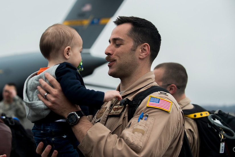 Capt. Michael Busse reunites with his son March 2, 2015, at Joint Base Charleston, S.C, during the 16th Airlift Squadron's redeployment from Southwest Asia. Aircrews from the 16th AS flew 1,902 sorties, logged more than 4,400 combat flying hours and airlifted more than 71 million pounds of cargo and 17,500 personnel during their two-month deployment.  (U.S. Air Force photo/Senior Airman Jared Trimarchi)