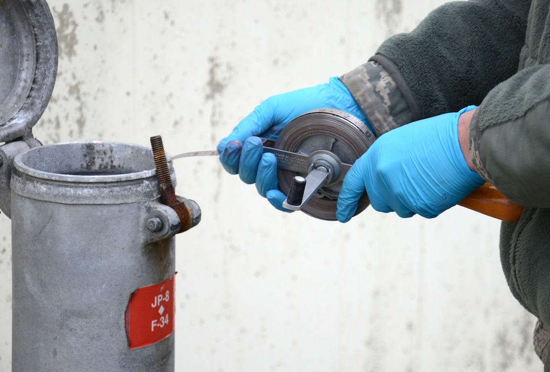 U.S. Air Force Airman 1st Class Daniel Lingefelt, 100th Logistics Readiness Squadron Fuels fixed facilities journeyman from Pendleton, S.C., verifies the fuel level in one of the base fuel tanks Feb. 11, 2015, on RAF Mildenhall, England. Lingefelt's shop manually gauges the tanks quarterly to ensure the automatic tank gauging system is providing accurate readings for the fuel they control. (U.S. Air Force photo by Gina Randall/Released)