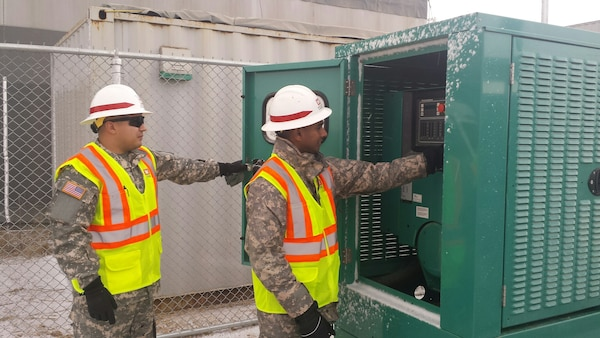 Sgt. Alfredo Alvarez (left) and Sgt. Dinesh Liyanage, members of the 249th Engineer Battalion - Prime Power, inspect a generator panel at a troop housing area construction site on U.S. Army Garrison Humphreys in February 2015. The Soldiers are on a 100 day temporary duty at the district providing expertise in electrical engineering.