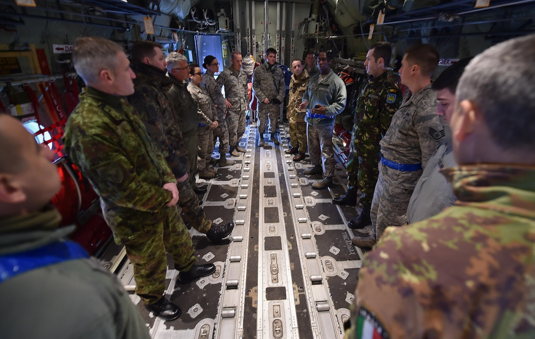 Tech. Sgt. James Shanks and Tech. Sgt. Chris Willingham brief a group of enlisted leaders from six different nations' air forces throughout Europe about the 86th Aircraft Maintenance Squadron mission inside a C-130J Hercules Feb. 23, 2015, at Ramstein Air Base, Germany. The group of enlisted leaders including the chief master sergeant of the Romanian and Estonian air forces and other leaders from the German, Italian, Slovenian and the U.K.'s air forces visited Ramstein AB before attending the Kaiserslautern Military Community First Sergeant Council's First Sergeant Symposium. Shanks and Willingham are both assigned to the 86th AMXS. (U.S. Air Force photo/Staff Sgt. Sara Keller)