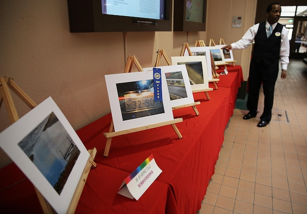 "Eugene Clark, the Youth & Teen Center coordinator aboard Marine Corps Air Station Iwakuni, Japan, reviews the artwork of contestants who entered the 2015 YTC Imagemakers Photography Exhibit at the Crossroads Mall, Feb. 25, 2015. Competitors from ages 9-18 showed various levels of photographic technique, skill and creativity. ""Our goal is to bring out the talent of the youth,"" said Eugene Clark, the YTC coordinator. ""We do our best to give children a creative outlet who find photography as their passion, not just as their classroom assignment."""